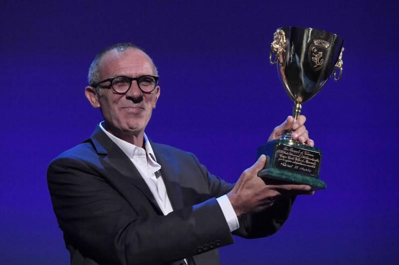 """Le 9 septembre 2017, Kamel el-Basha sur la scène de la Mostra de Venise brandissant son trophée du meilleur acteur pour son rôle dans """"L'Insulte""""."""